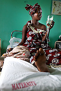 A woman holds her own IV fluid in the maternity ward in a Senegal hospital.