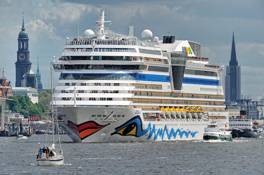 """Die """"Aida sol"""" läuft aus dem Hafen Hamburg aus und ist umringt von Barkassen. Im Hintergrund ist der Turm vom Michel, Rathaus und St. Nikolai zu sehen."""