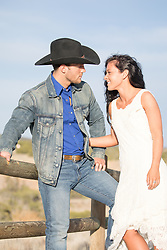 cowboy and a beautiful girl outdoors on a ranch