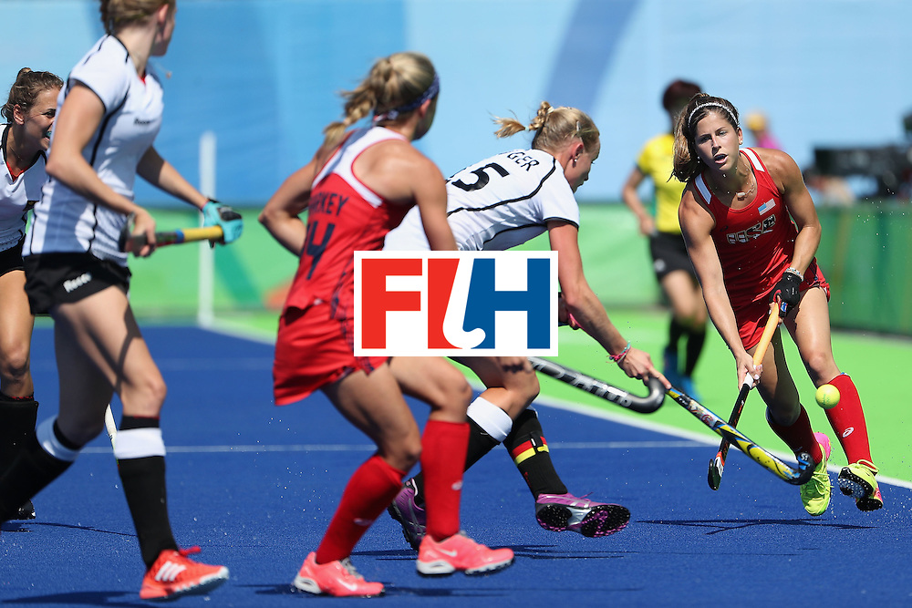 RIO DE JANEIRO, BRAZIL - AUGUST 15:  Katie Reinprecht #14 of United States moves the ball past Hannah Kruger #15 of Germany during the quarter final hockey game on Day 10 of the Rio 2016 Olympic Games at the Olympic Hockey Centre on August 15, 2016 in Rio de Janeiro, Brazil.  (Photo by Christian Petersen/Getty Images)