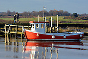 © Licensed to London News Pictures. 01/12/2013. Southwold, UK. A fishing boat sits in the harbour in the early sunshine. The first of December was greeted by a brisk sunny morning at the harbour on the River Blyth in Southwold, Suffolk today, 1st December 2013. Photo credit : Stephen Simpson/LNP