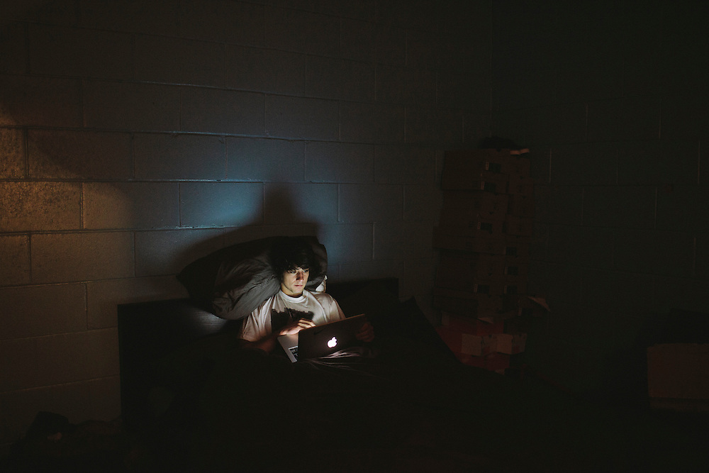 Kriss Kyle settles down with his laptop in his makeshift bedroom within Unit 23.
