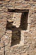 T-shaped stone wall opening. Pueblo Bonito is a monumental public building (Puebloan Great House) occupied from around 828 to 1126 AD, now preserved at Chaco Culture National Historical Park, New Mexico, USA. The huge D-shaped complex of Pueblo Bonito enclosed two plazas with dozens of ceremonial kivas, plus 600 rooms towering 4 and 5 stories above the valley floor. The functions of this building included ceremony, administration, trading, storage, hospitality, communications, astronomy, and burial, but few living quarters. Chaco Culture NHP hosts the densest and most exceptional concentration of pueblos in the American Southwest and is a UNESCO World Heritage Site, located in remote northwestern New Mexico, between Albuquerque and Farmington. From 850 AD to 1250 AD, Chaco Canyon advanced then declined as a major center of culture for the Ancient Pueblo Peoples. Chacoans quarried sandstone blocks and hauled timber from great distances, assembling fifteen major complexes that remained the largest buildings in North America until the 1800s. Climate change may have led to its abandonment, beginning with a 50-year drought starting in 1130.