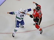 Derek Dorsett #15 of the Vancouver Canucks drops the gloves against Michael Ferland #79 of the Calgary Flames in the first 2 seconds of the season opener at Scotiabank Saddledome on Wednesday, October 7, 2015 in Calgary, Alberta, Canada. (Photo by Jenn Pierce/NHLI via Getty Images)