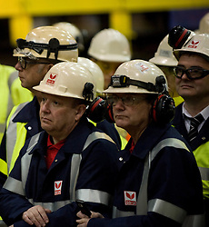 © Licensed to London News Pictures. 18/04/2012..SSI Steel, Teesside, England..Steel workers looks on as they wait for the first slab of steel to come through the cutting machine...Two years after the closure of the Corus steel production plant, the huge blast furnace on the site in Teesside was re-lit at the weekend as the process of bringing the furnace back to operating temperature begins...Today, the furnace, now owned by the Thai company Sahaviriya Steel Industries saw the first steel slabs come out of the furnace. ..The steel will now be shipped direct to SSI in Thailand for use in the car or white good industries...Photo credit : Ian Forsyth/LNP