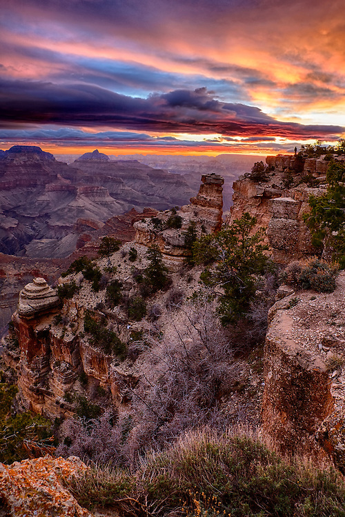 A lone figure stands on the edge of the South Rim of the Grand Canyon taking in the world around her at sunrise