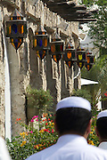 Men walking, colorful lamps overhead