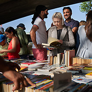 People browse books in a street market in front of the Thames River in London, United Kingdom.