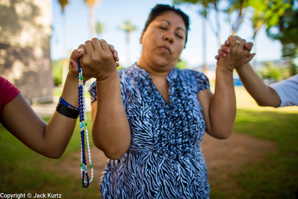18 JUNE 2012 - PHOENIX, AZ:  A woman joins hands with others and prays during a vigil against SB 1070 Monday. About 20 people, members of the immigrant rights' group Promise AZ (PAZ) held a prayer vigil at the Arizona State Capitol in Phoenix Monday praying that the US Supreme Court would overturn SB 1070, Arizona's controversial anti-immigrant law. The court's ruling had been expected Monday, June 18 but the the court said the ruling would not come out until later this month. Members of PAZ said they would continue their vigil until the ruling was issued.   PHOTO BY JACK KURTZ