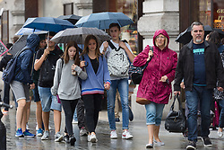 © Licensed to London News Pictures. 23/07/2017. LONDON, UK.  People are caught in a rain shower in Regent Street in London during a spell of wet weather this afternoon.  Photo credit: Vickie Flores/LNP