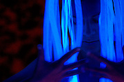 A young woman wearing a glowing dreadlock headpiece collects her thoughts before going to a party.Black light