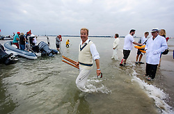 © Licensed to London News Pictures. 18/09/2016. Portsmouth, UK. The wickets being carried off after the game. Teams take part in the  Bramble Bank Cricket Match in the middle of The Solent strait on September 18, 2016. The annual cricket match between the Royal Southern Yacht Club and The Island Sailing Club, takes place on a sandbank which appears for 30 minutes at lowest tide. The game lasts until the tide returns. Photo credit: Ben Cawthra/LNP