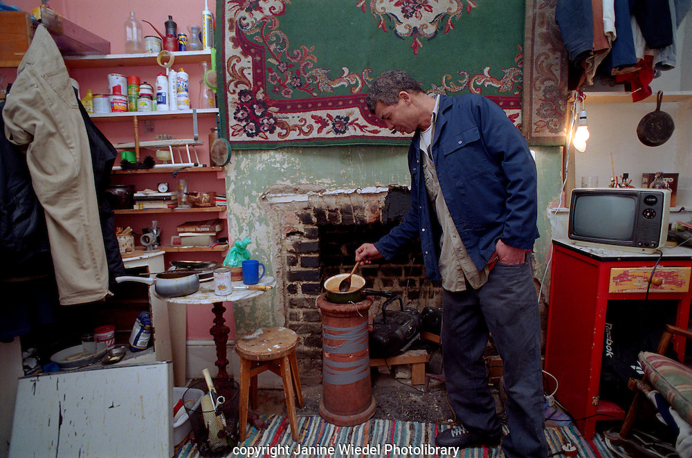 Middle aged man cooking his meal in his room in squat in Saint Agnes Place kennington London.