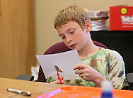 Quentin Strohm, 10, of Ames, works on cutting out his shrinky dinks craft during a summer camp hosted by the Iowa School for the Deaf at the Iowa Braille and Sight Saving School in Vinton on Tuesday, July 16, 2013.