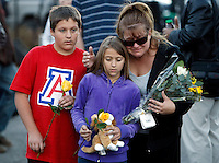 A family arrives to place flowers and a stuffed animal at a memorial outside the hospital where victims of yesterdays shootings are recovering in Tucson, Arizona January 9, 2011.  REUTERS/Rick Wilking (UNITED STATES)