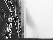 Heavy fog obscures the massive structure of the Golden Gate Bridge as it disappears into the distance. Two figures take in the scene from the ramparts of Fort Point, San Francisco.<br />