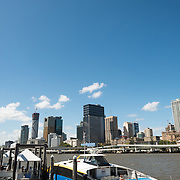 A Citycat ferry pulled up to a ferry terminal at South Bank, with the Brisbane city skyline in the background from across the Brisbane River. Citycat's provide a public transport option for using the river that winds through the center of the city.