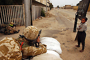 Basra, Iraq--  April 7, 2003   A young boy watches with amusement as two Royal Scotts Dragoons Guards  take cover and aim down a street near the Basra General Hospital.  Photo by essdras m suarez/globe staff