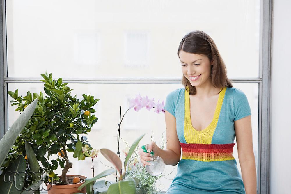 Woman spraying flowers by window