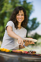 Woman Grilling Food at Park portrait.