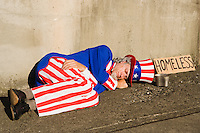 "Uncle Sam asleep on a sidewalk with a sign reading ""homeless"" next to him."