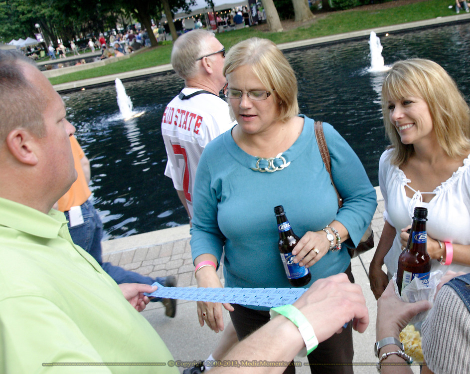 Kettering-Moraine-Oakwood Chamber of Commerce membership chair Kevin Jones (left) measures off raffle tickts during the 21st annual The Taste in the Lincoln Park Commons area at the Fraze Pavilion, Thursday, September 3, 2009.