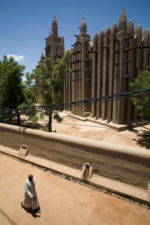 "A man dressed with a ""bubu"" passes by Mopti's Great Mosque. At the confluence of the Niger and the Bani rivers, between Timbuktu and Segou, Mopti is the second largest city in Mali, and the hub for commerce and tourism in this west-african landlocked country."