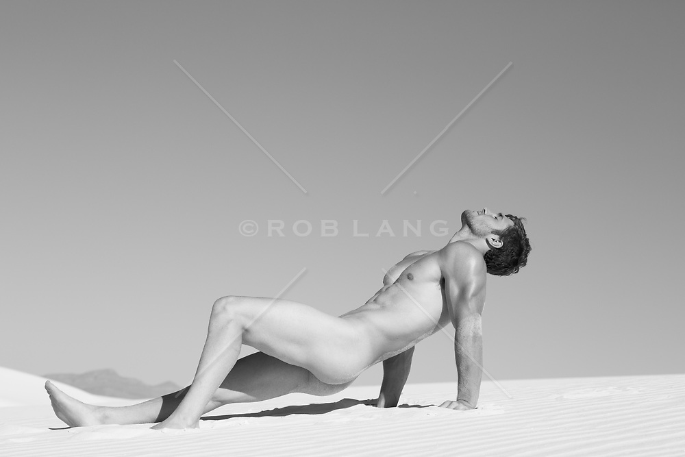 nude muscular man on a sand dune