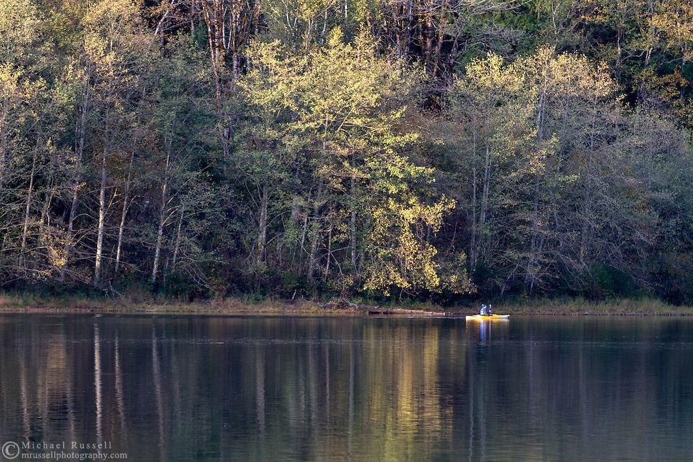 A man in a kayak paddles along the shore of Deer Lake in Sasquatch Provincial Park, British Columbia, Canada.