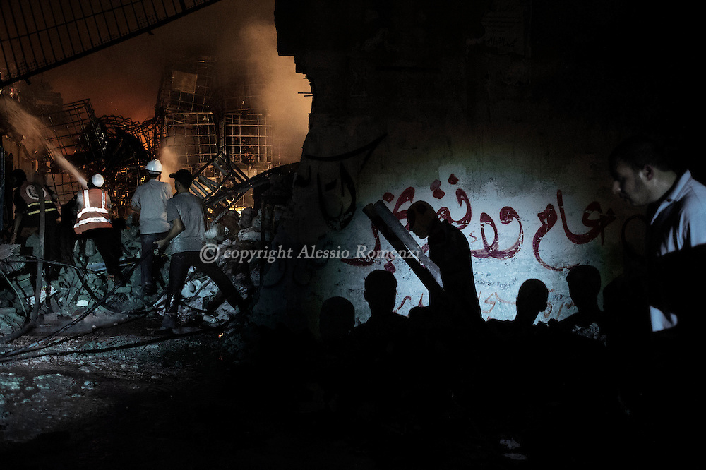 Gaza Strip, Gaza City: Firefighters try to shut off a fire inside a soap factory in Gaza City after was hit by an Israeli airstrike on August 10, 2012. ALESSIO ROMENZI