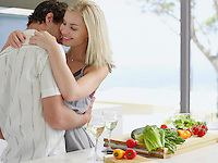 Young couple hugging in kitchen near countertop with fresh produce and wineglasses