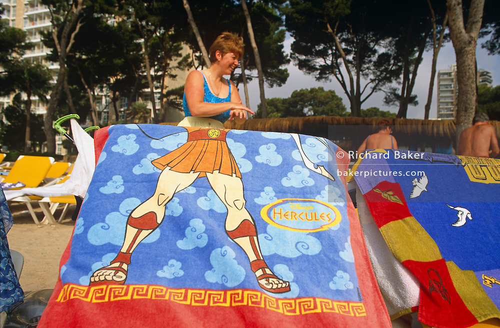 A British lady applies a layer of sun cream to her hand on a beach in Magaluf.  In the foreground, and aligned with the lady's own body is a sun lounger with a beach towel draped over which depicts the torso and legs of a cartoon Hercules Adonis character complete in ancient Greek style with muscular thighs and short skirt. In the background is a hotel building and two other tourists with their tanned backs towards the viewer. Magaluf is a popular holiday resort on the island of Mallorca, one of the Spanish Balearic Islands. A seedy resort very much orientated around British tourists and catering for both young parties as well as families, it is considered as a hot and exotic alternative to the chilly seaside towns around the UK's coast.  .