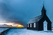 A brief flash of light in the distance at sunrise as the sun finds a small break in the clouds behind the Black Church near Biður, Iceland.