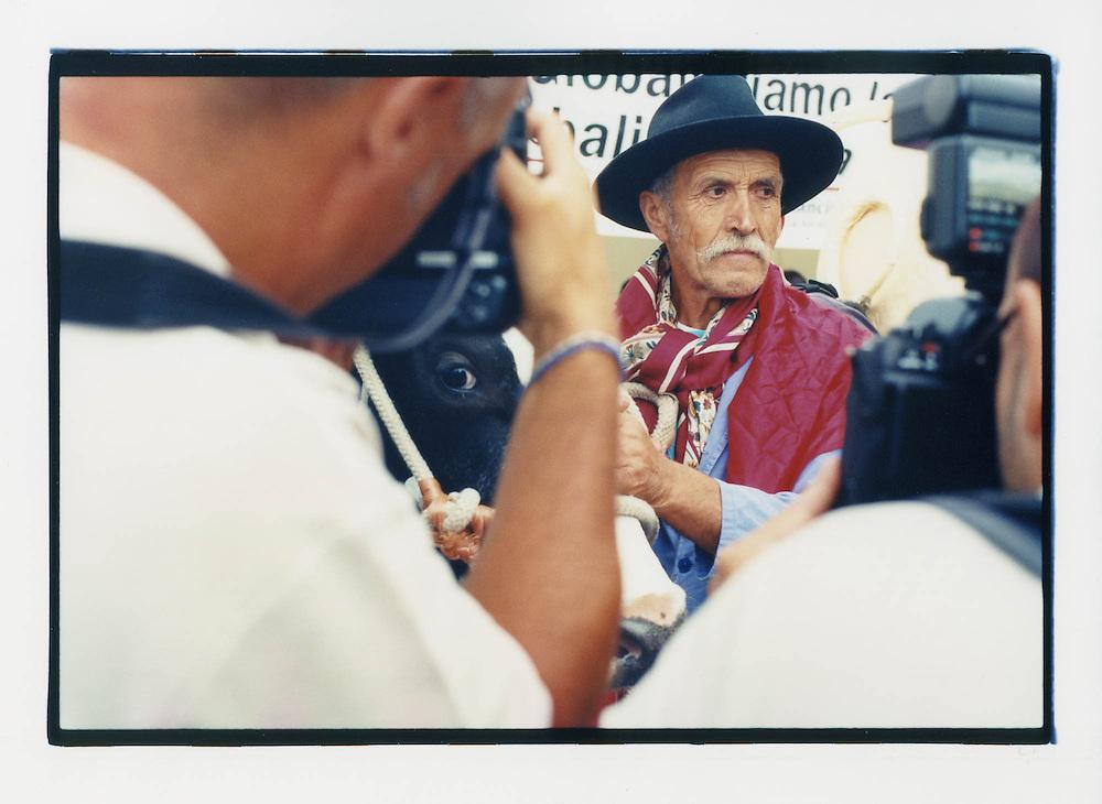 """Proteste contro il summit del G8, Genova luglio 2001. Piazza Rossetti (Foce), 18 luglio. La """"Mucca Carolina"""" dei Cobas Latte sotto l'occhio dei fotogiornalisti."""