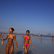 Local Brazilian teenage girls walk along Sao Conrado beach as local boy's play football in the background, Rio de Janeiro,  Brazil. 8th July 2010. Photo Tim Clayto..