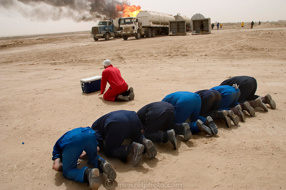 "Firefighters from the Kuwait Oil Company (called KWWK: Kuwait Wild Well Killers) pray at noon by the first oil well fire they were working on in Iraq's Rumeilah Oil Field. They did a double prayer at noon so they would not have to stop later in the day if they were at a critical phase. Later in the day they extinguished this smoky fire and the next day stopped the flow of gas and oil with drilling mud using what is called a ""stinger"", a tapered pipe on the end of a long steel boom controlled by a bulldozer. Drilling mud, under high pressure, is pumped through the stinger into the well, stopping the flow of oil and gas. (Supporting image from the project Hungry Planet: What the World Eats.)"