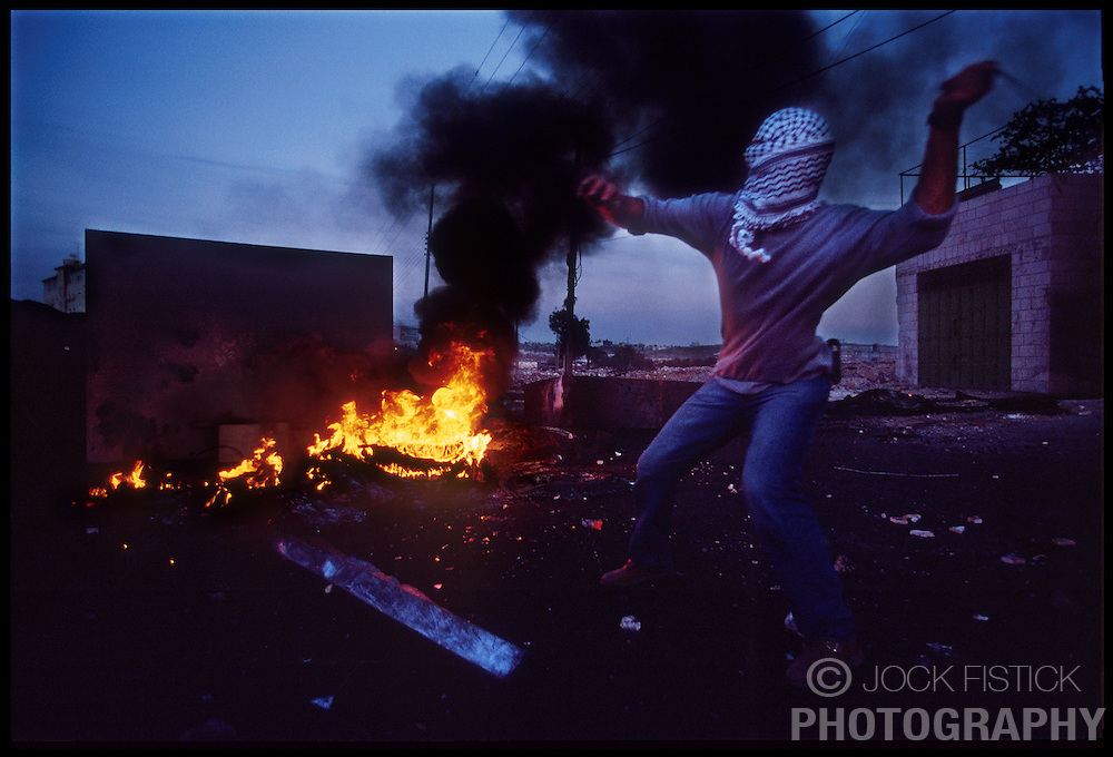 A Palestinian youth uses a sling to throw stones at Israeli soldiers during a clash in the West-bank city of Ramallah. (Photo © Jock Fistick)