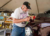 "Russ Mowry of Candia works on a ""bagger"" Harley Davidson at his pinstriping tent in front of Thurston's Marine at Weirs Beach Thursday afternoon.  (Karen Bobotas/for the Laconia Daily Sun)"