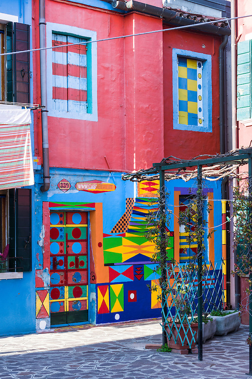 traditional houses in burano are painted in bright colours and can be seen with laundry hanging outside. this is the most fanous house known as casa di bepi sua