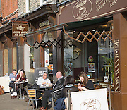 People sitting at tables outside Benets cafe, King's Parade, Cambridge, England
