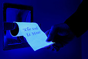 "A hand tugs on a glowing roll of toilet paper that is marked ""The End Is Near"".  Blacklight photography."