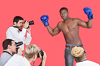 Paparazzi taking photographs of male boxer over red background