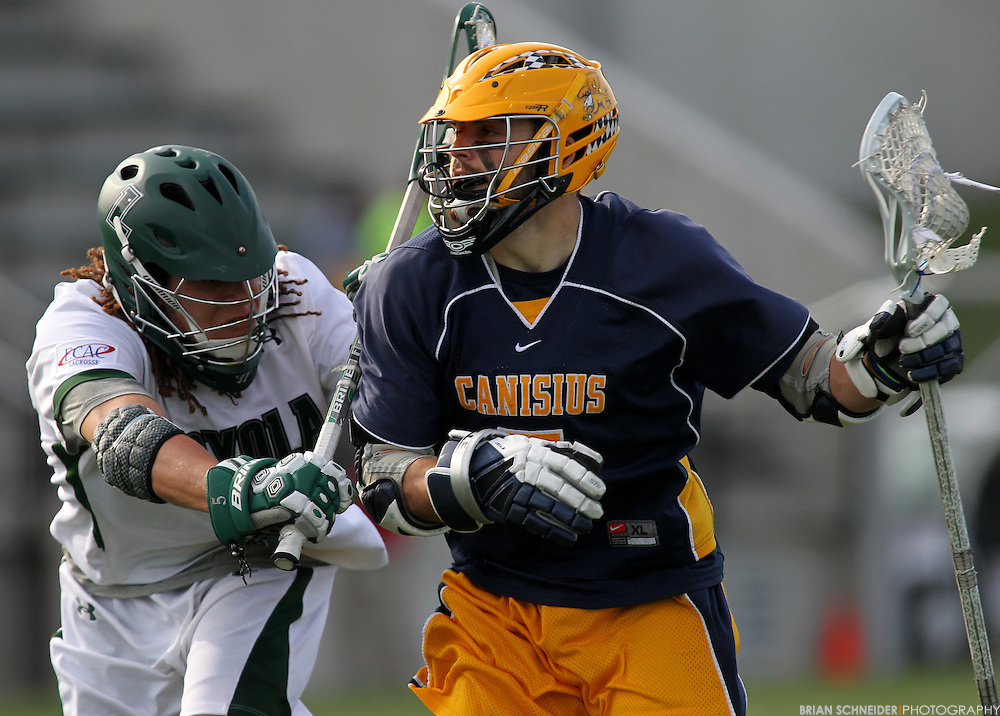 May 12, 2012; Baltimore, MD, USA; Canisius College Golden Griffins attack Cody Gould (5) against Loyola Maryland Greyhounds midfielder Josh Hawkins (5) at Ridley Athletic Complex in Baltimore, MD. Mandatory Credit: Brian Schneider-www.ebrianschneider.com