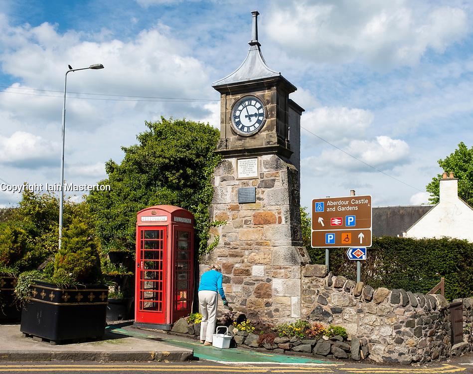 Woman tending to garden at clocktower in centre of Aberdour village in Fife, Scotland, UK