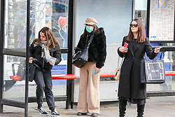 © Licensed to London News Pictures. 01/03/2020. London, UK. A woman wearing a surgical face mask waits at a bus stop in Westminster, as a precaution against new type coronavirus (COVID-19). Twelve more people have tested positive for coronavirus in the UK, bringing the total number of cases to 35. Photo credit: Dinendra Haria/LNP