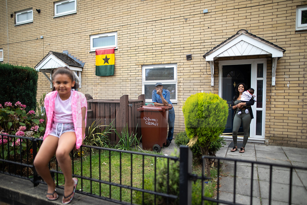 © Licensed to London News Pictures . 11/08/2018. Manchester , UK . Residents on Quinney Crescent watch the procession as is passes through Moss Side . The annual Moss Side Caribbean Carnival procession , celebrating dance , music and Afro-Caribbean culture , which passes in a loop from Alexandra Park and through the streets of Moss Side . Photo credit : Joel Goodman/LNP