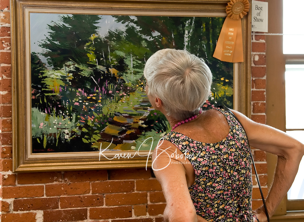Visitors and artists enjoyed browsing the display of artwork for the 70th annual Lakes Region Art Association Show at the Belknap Mill on Sunday afternoon.  (Karen Bobotas/for the Laconia Daily Sun).
