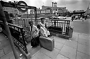Two women and a girl emerge from the underground, Kings Cross Tube Station, London, UK, 1980s.