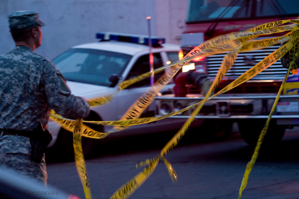 National Guard taking down crime scene tape after a crime scene has been cleared in the 9th Ward, shot while riding along with the National Guard in New Olreans as they do their job partolling the city.