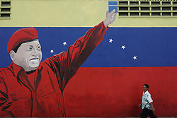A woman walks by a mural of Hugo Chavez holding the Venezuela constitution on a wall in the slum of Catia, across the street from Mercal, a government sponsored subsidized food market.  The Chavez government has built many of these markets throughout Venezuela.  It is one of the many social programs that Chavez saysaids the poor. Opponents claim that these programs  are not sustainable and are really aimed at gaining support for Chavez.